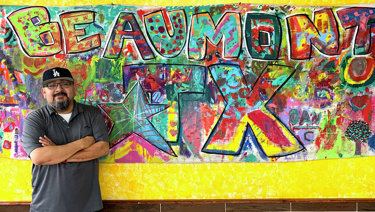 Carlos Zuniga poses in front of a mural painted by children that hangs on the wall of Tacos La Bamba. Photo by Andy Coughlan