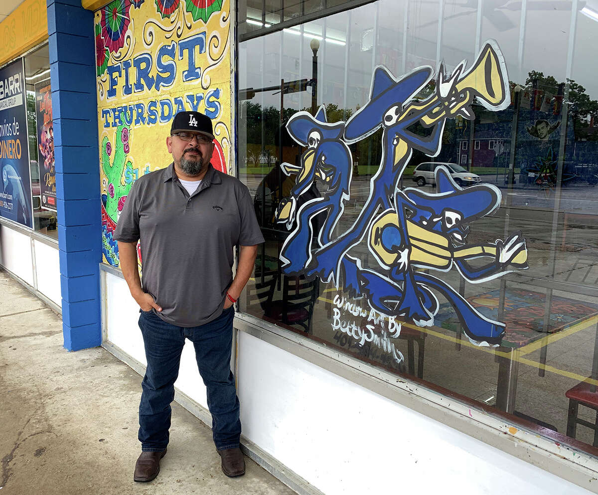 Carlos Zuniga with Betty Smith's painted window at Tacos La Bamba. Photo by Andy Coughlan