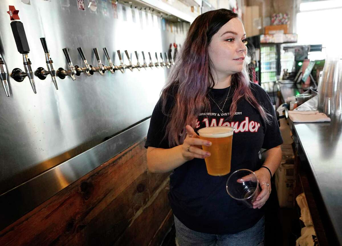 Allyson Boyd, a taproom manager, serves beer at 8th Wonder Brewing, 2202 Dallas St., Thursday, Sept. 16, 2021 in Houston. A new jobs report is expected to show moderate gains in the service industry.
