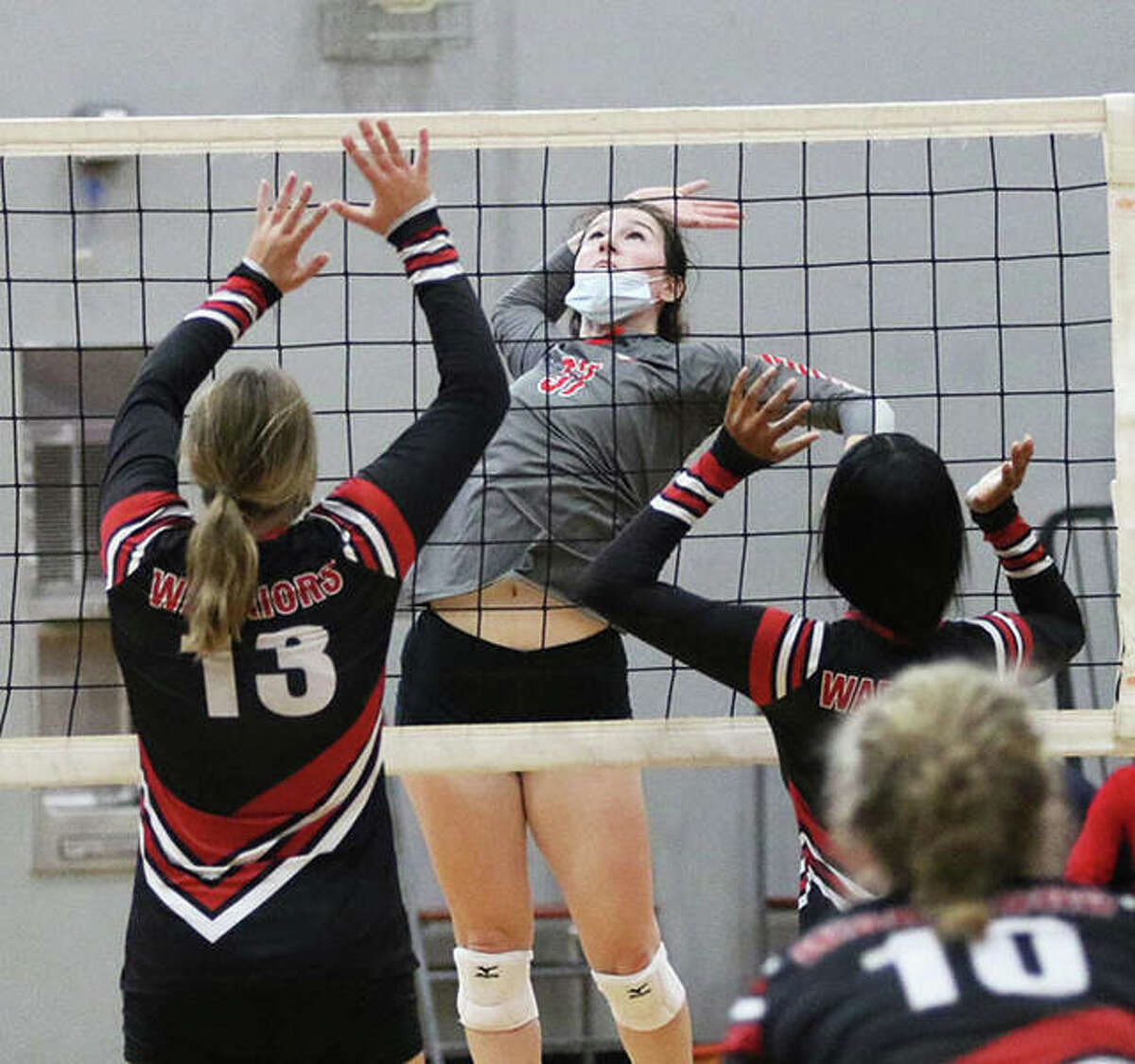 Alton's Reese Plont, (middle) shown in a match against Granite City in last weekend's Alton Tourney, had seven kills in the Redbirds' SWC win over Collinsville on Thursday night in Godfrey.