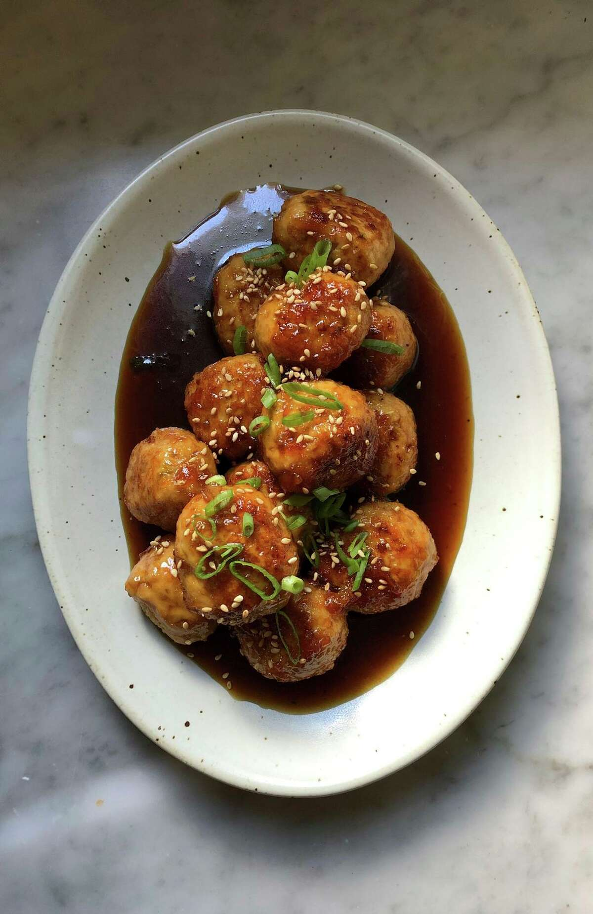 Chicken meatballs are bathed in a four-ingredient glaze that includes light-bodied soy sauce and orange marmalade.