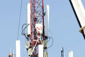 It wasn't a job for anybody afraid of heights but two telecommunications workers were hanging from the Godfrey cellular tower, about 100 feet in the air, near the end of Bryden Lane Thursday to replace all three sides of the cellular platform and the antennas attached to them.