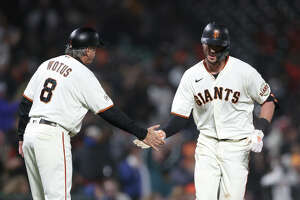 Kris Bryant of the San Francisco Giants is congratulated by third base coach Ron Wotus after he hit a home run in the sixth inning against the San Diego Padres