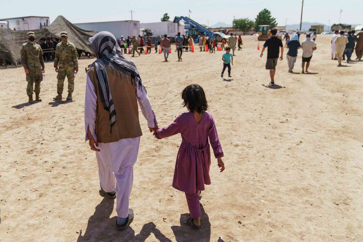 A man and child through Doña Ana Village in Fort Bliss, N.M., where Afghan refugees are being housed. Countless others remain trapped in Afghanistan, fearful of Taliban retribution.