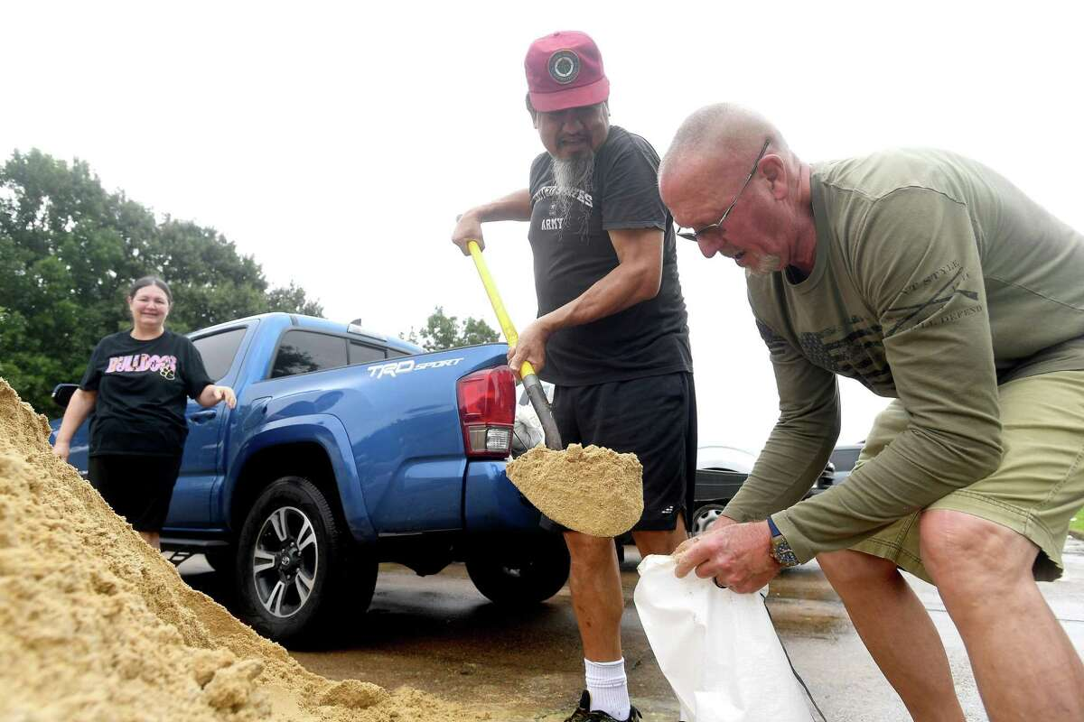 From left, Janet and Rafael Posadas and Monty Mozley fill sandbags just after a site was opened in Doornbos Park in Nederland Monday morning. With Tropical Storm Nicholas expected to make landfall later in the day before tracking east, residents across the area prepared for possible flood impacts. Photo made Monday, September 13, 2021 Kim Brent/The Enterprise