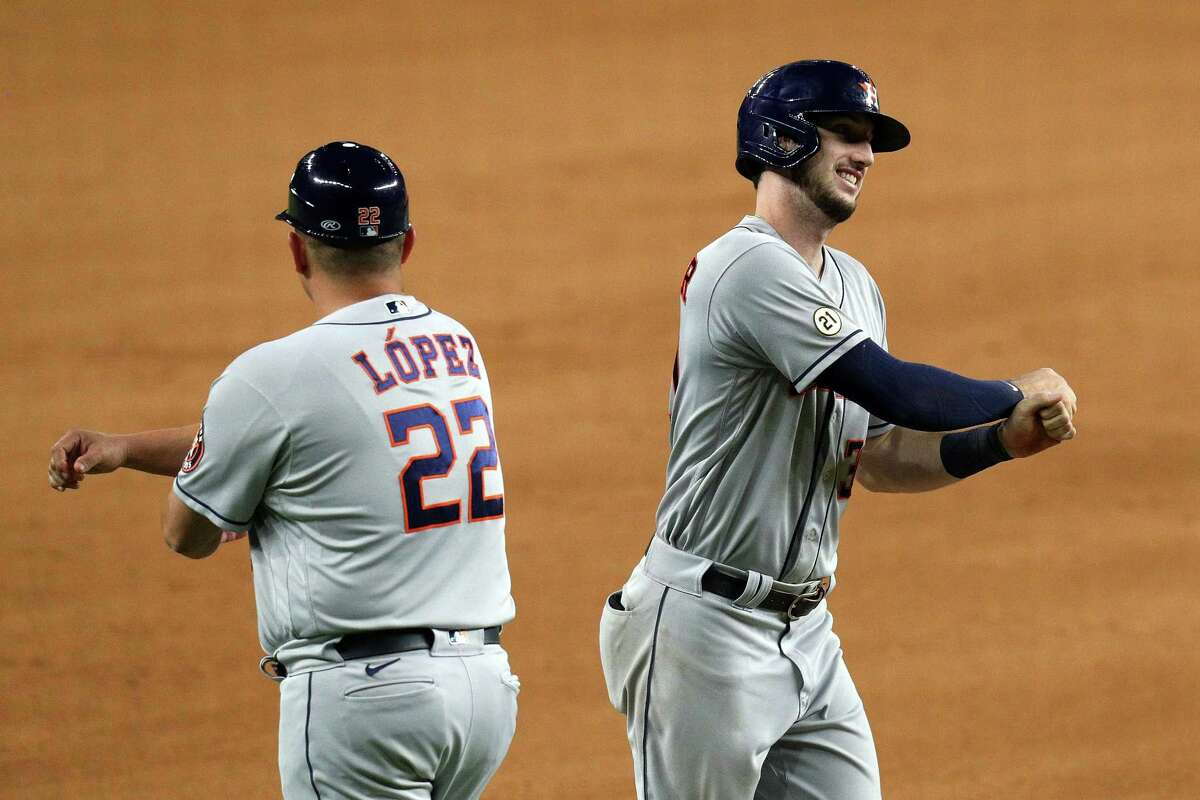 Third base coach Omar Lopez #22 celebrates the solo home run by Kyle Tucker of the Houston Astros in the eighth inning against the Texas Rangers at Globe Life Field on September 15, 2021 in Arlington.