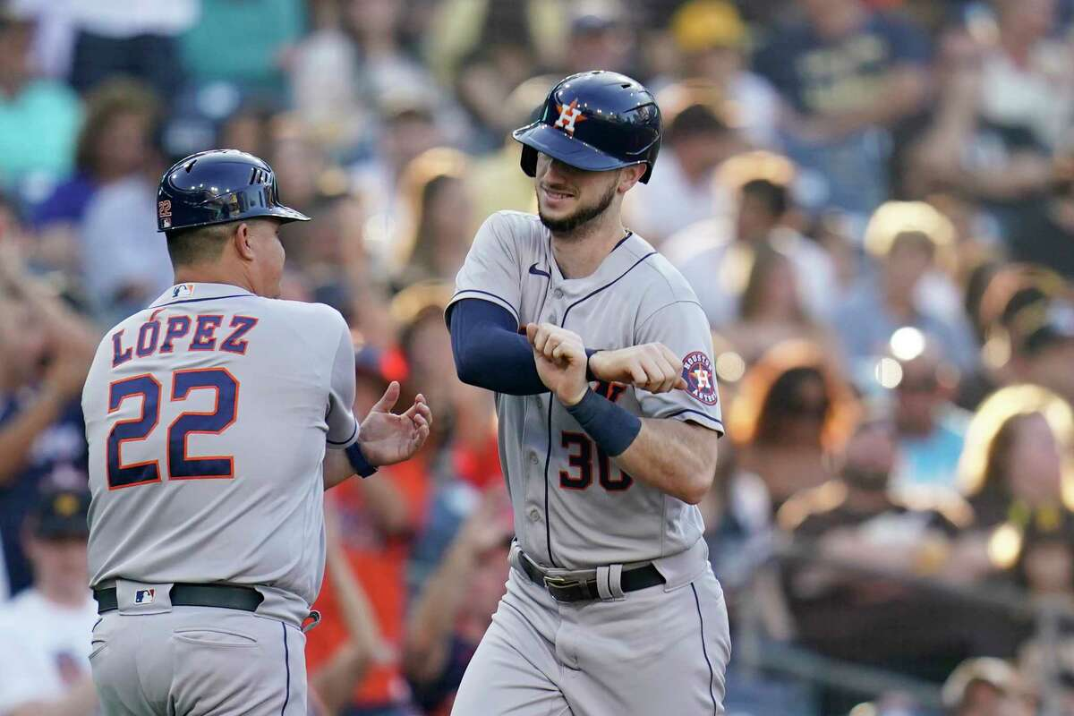 Houston Astros' Kyle Tucker, right, reacts with first base coach Omar Lopez (22) after hitting a home run during the second inning of a baseball game against the San Diego Padres, Saturday, Sept. 4, 2021, in San Diego. (AP Photo/Gregory Bull)