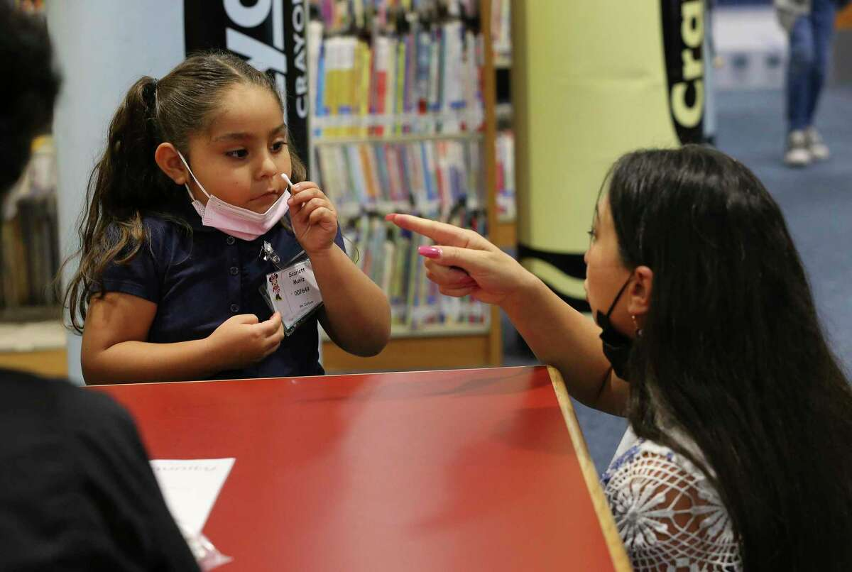 Olga Moucoulis, Edgewood Independent School District's executive director for industry and community partnership, helps a young student with a COVID-19 swab as Community Labs conducts coronavirus testing at Roosevelt Elementary on Wednesday, Sept. 15, 2021.