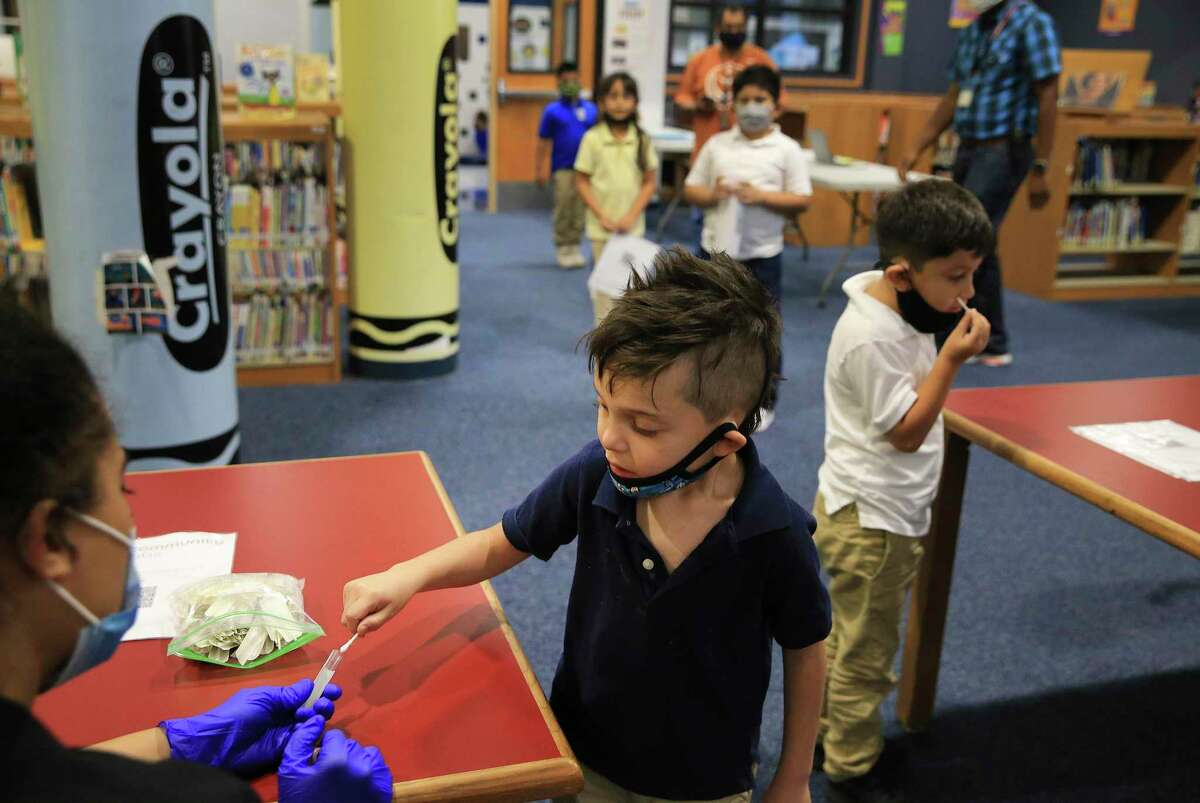 A young boy joins fellow classmates in testing for COVID-19 as Community Labs collects samples to test at Roosevelt Elementary in the Edgewood ISD on Sept. 15.