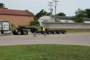 In this file photo, a beam is delivered to the site of the M-55 bridge project in July. Four beams are scheduled to be delivered Monday and the final four are expected to come Tuesday. (File photo)