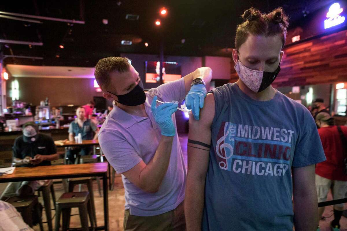 Ruston Taylor administers a dose of Moderna COVID-19 vaccine to Austin Houghton during a pop-up vaccination clinic at BUDDY'S Houston in Montrose on Thursday, April 29, 2021 in Houston. BUDDY'S teamed up with Wellness Bar by Legacy to offer vaccines by appointment.