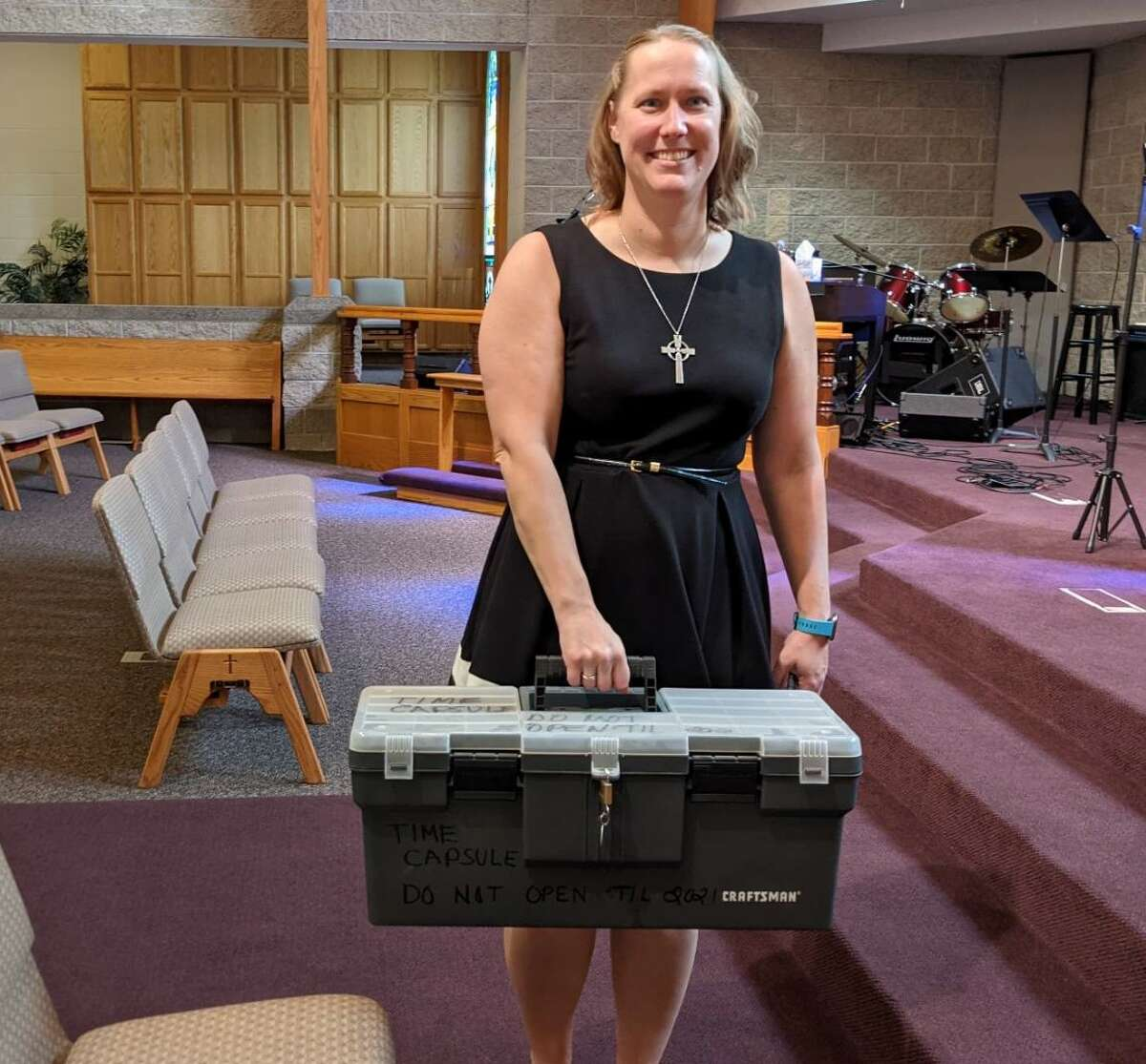 Freeland United Methodist Church Pastor Kayla Roosa holds the time capsule that will be open Sunday, Sept. 19. The capsule, a tackle box, was buried 25 years ago during the church's 150 celebration.