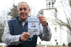 """Former Southbury First Selectman Ed Edelson poses with a copy of his book, """"Lois's Story: A Young Girl's Inspiration Helps to Stop Hate and Fear"""", in front of South Britain Congregational Church, in Southbury, Conn. Dec. 30. 2020."""