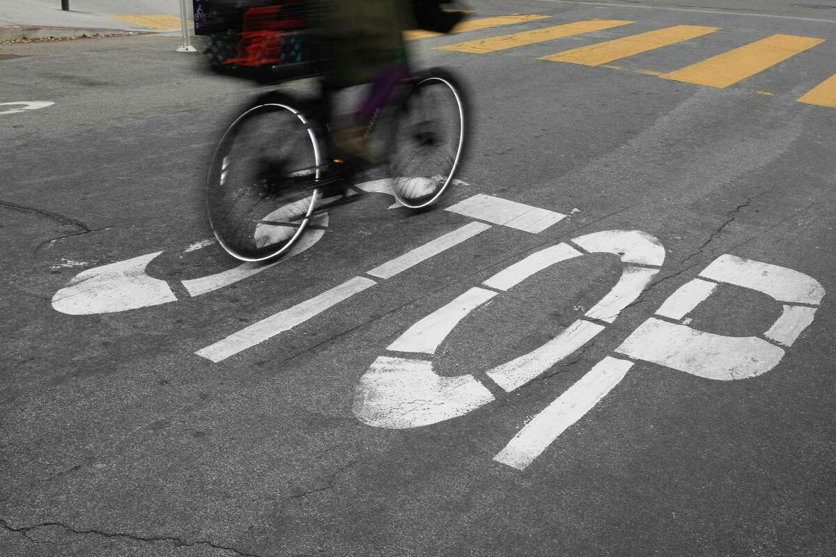 A bicyclist rolls through a stop sign last week on Page Street in S.F. California could become the latest state to allow cyclists to legally treat stop signs as yield signs, known as an Idaho stop.