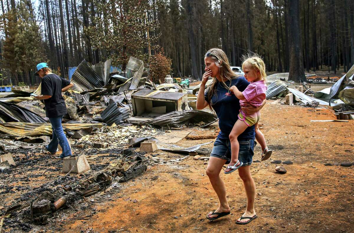 Candance Tyler and daughters Amber (left) and Lily survey the Caldor Fire's destruction of their home in Grizzly Flats.