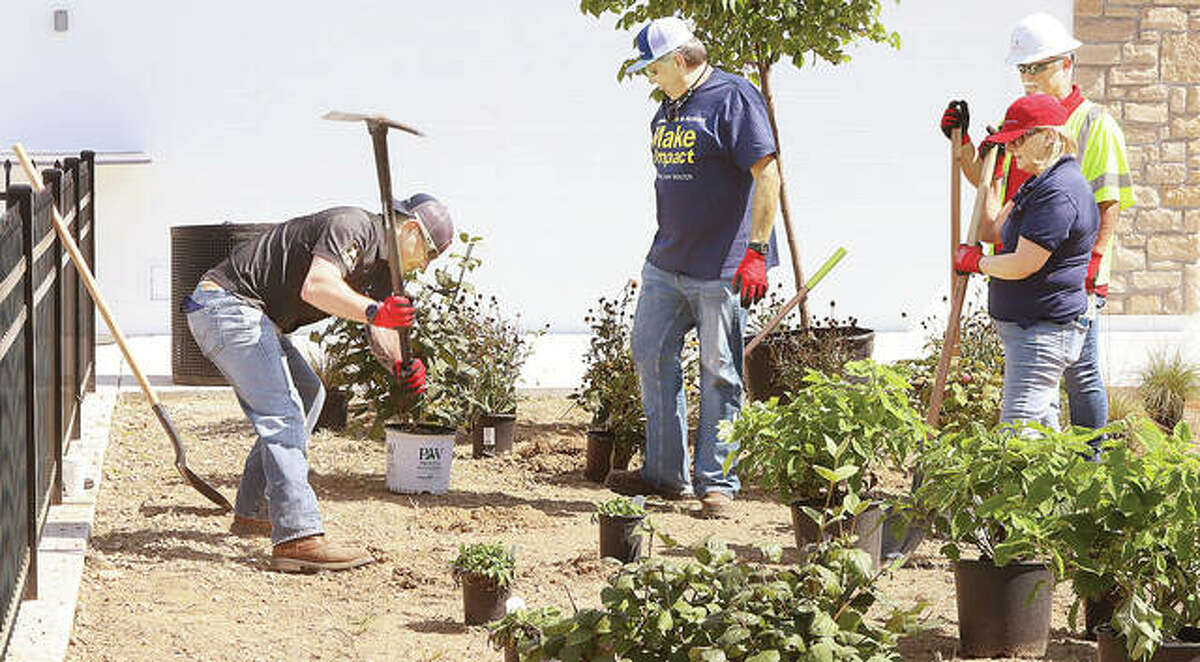 Faced with rock-filled dirt, Illinois American Water Company volunteers at a splash pad beautification project had to resort to use a pick to start turning the earth for planting Friday in Riverfront Park. The group planted dozens of shrubs, flowers, grasses and small trees.