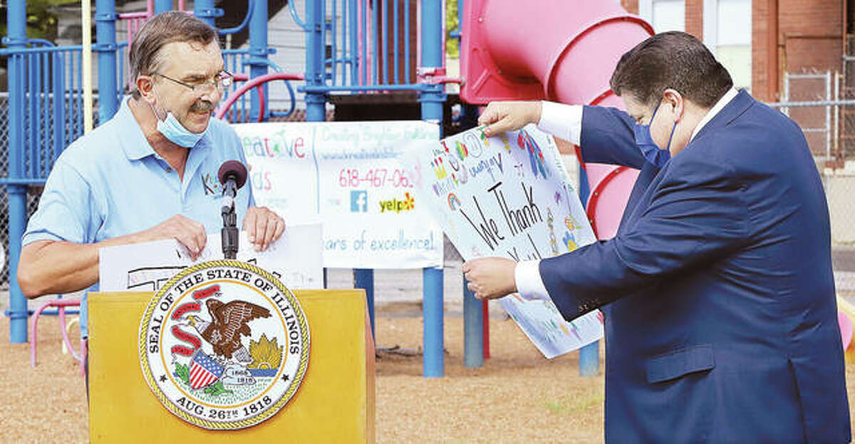 """Kreative Kids Learning Center CEO Keith Neuber, left, presents Gov. J.B. Pritzker with two large """"Thank You"""" cards signed by students at the daycare facility. Pritzker and other state leaders visited the Alton facility Friday to promote the state's child care investments in the Metro East."""
