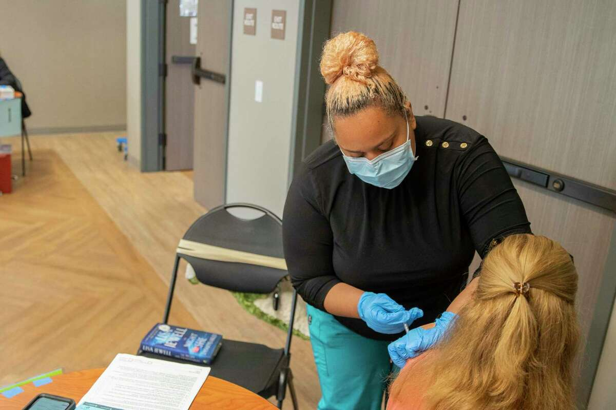 Khrizia Allen, left, administers the Pfizer vaccine at the Mountain View Community Center on Wednesday in Mountain View.