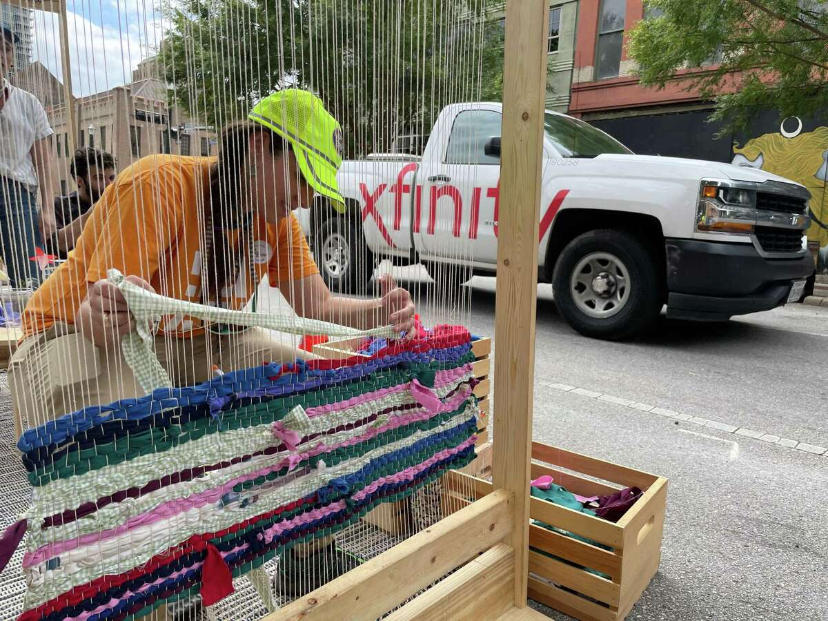 Laura Rocha with Houston Public Works weaves fabric during a Park(ing) Day event in downtown Houston on Sept. 17, 2021. The event raises awareness to the space used by cars and trucks by converting parking spaces to small parks.