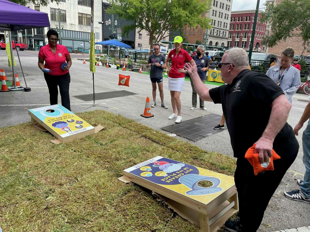 Houston City Council members Martha Castex-Tatum, left, and David Robinson, right, play cornhole as Council Member Sallie Alcorn, center, watches during a Park(ing) Day event in downtown Houston on Sept. 17, 2021. The event raises awareness to the space used by cars and trucks by converting parking spaces to small parks.