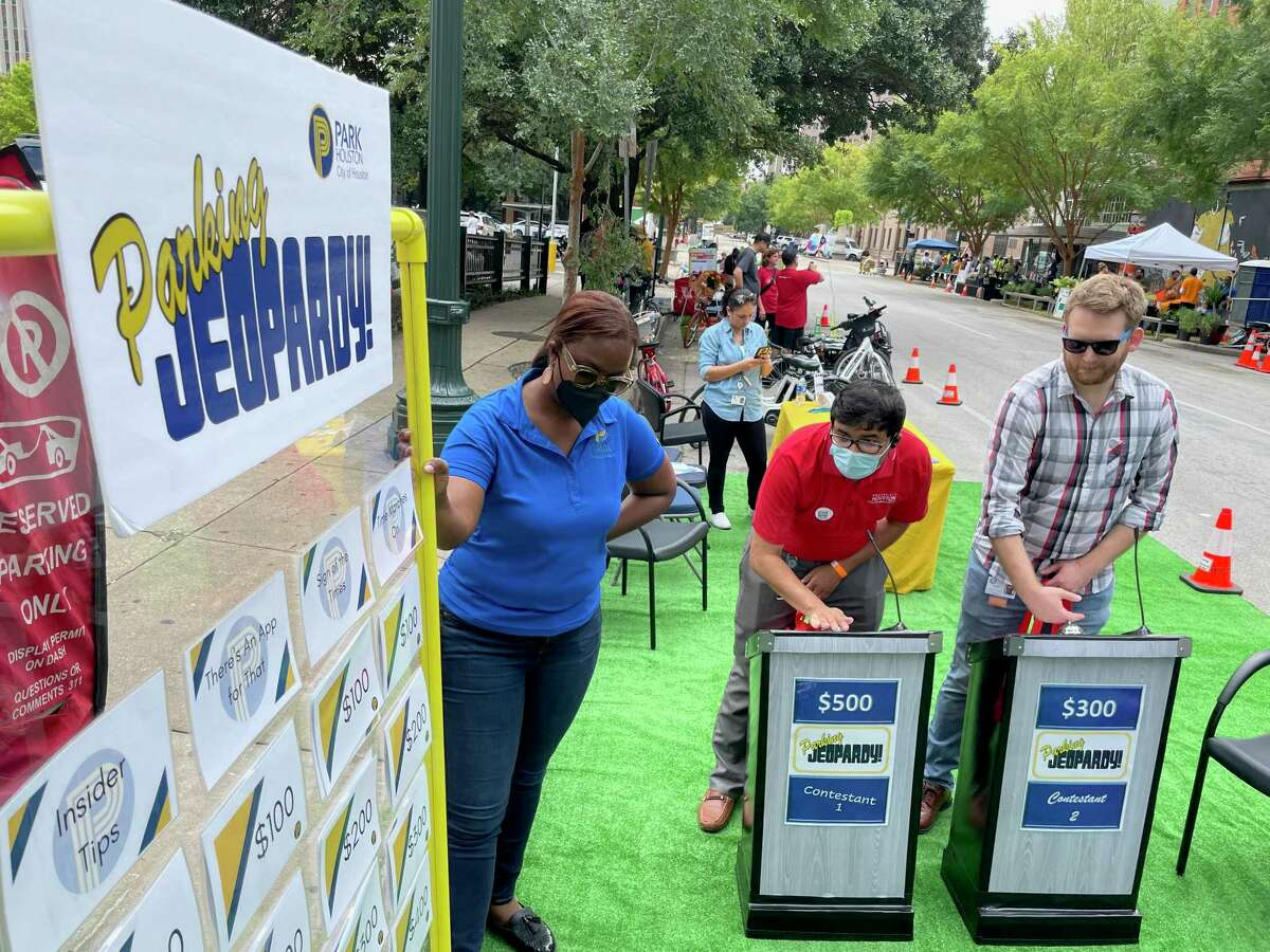 """Tanzeem Chowdhury, center, and Brian Schrock, right, both with Houston Public Works compete in """"Parking Jeopardy,"""" a trivia game of parking rules, during a Park(ing) Day event in downtown Houston on Sept. 17, 2021. The event raises awareness to the space used by cars and trucks by converting parking spaces to small parks."""