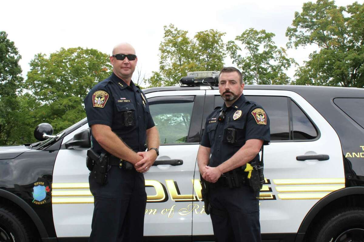 Ridgefield Police Chief Jeff Kreitz, left, and Lt. Nick Fowler stand in front of a patrol car that is outfitted with an Axon dashboard camera. The department rolled out both in-car and body cameras earlier this month to comply with the state's police accountability bill mandate.