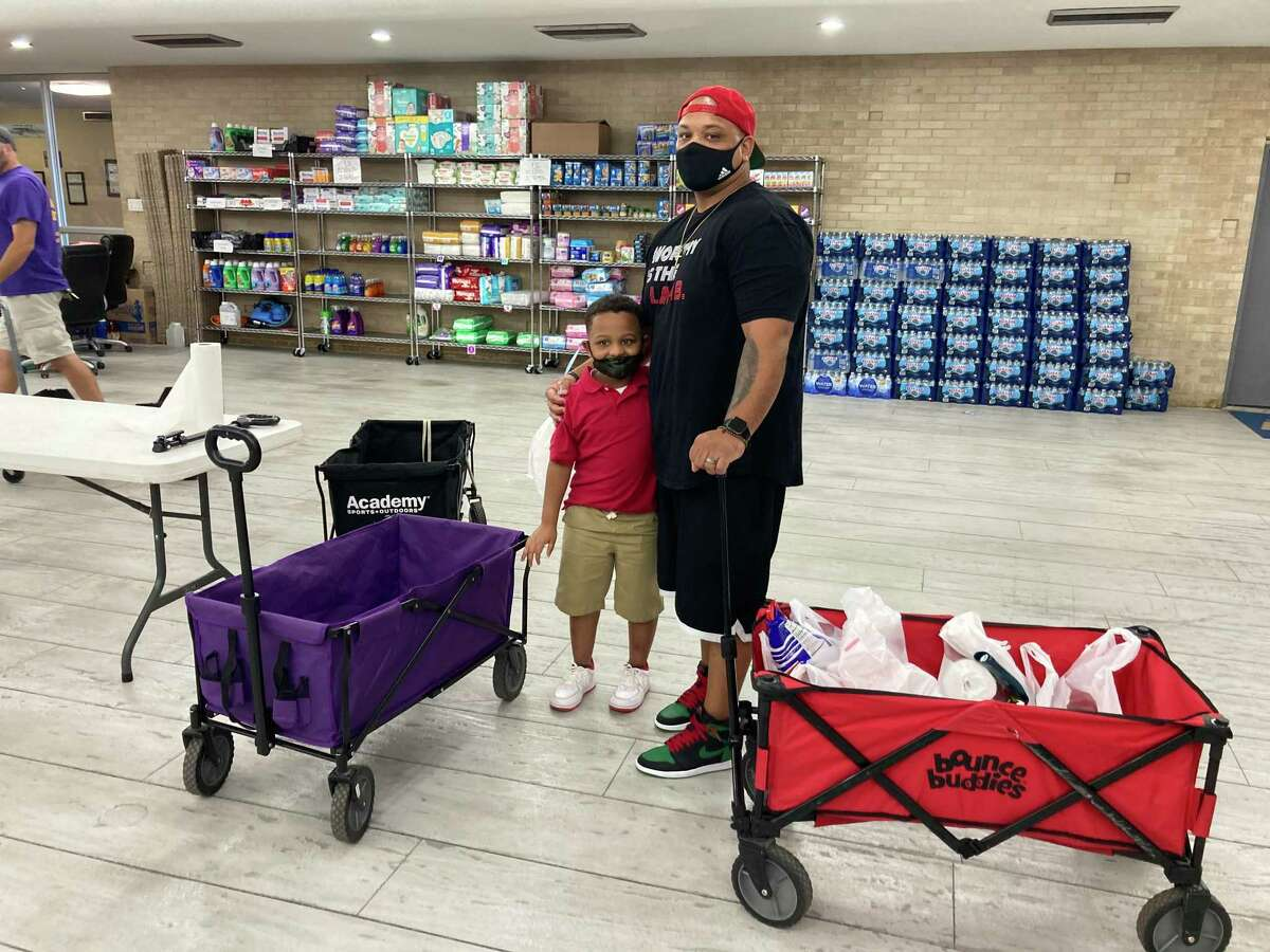 Lance Lastrape and his son, Jayce Lastrape, picking out household goods at the pantry United Steelworkers set up for workers affected by the lockout. Lance has been working for the ExxonMobil plant for 16.5 years.