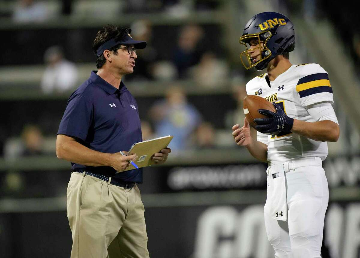 Northern Colorado coach Ed McCaffrey, left, confers with quarterback Dylan McCaffrey, his son, during the second half of the team's NCAA college football game against Colorado on Friday, Sept. 3, 2021, in Boulder, Colo. Colorado won 35-7. (AP Photo/David Zalubowski)