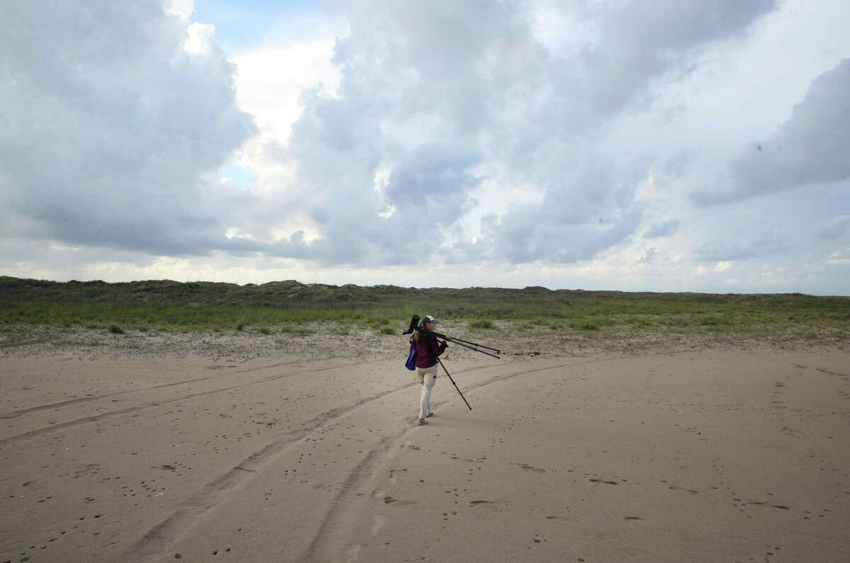 """Stephanie Bilodeau, a coastal bird biologist known to SpaceX security as the """"bird lady,"""" carries her spotting scope through mudflats near the SpaceX launch facility on Thursday, June 17, 2021, in Boca Chica. """"It just concerns me a bit, what that's going to look like and how that's going to impact the birds nesting out here,"""" she said. """"There's a reason they want to nest here, and it's just unfortunate if they're forced to move elsewhere."""""""