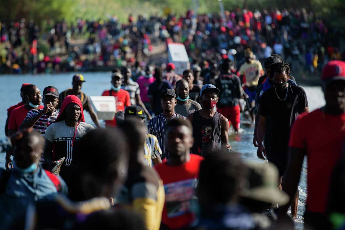 Migrants, many of whom are from Haiti, cross the Rio Grande from Del Rio back to Ciudad Acuña, Mexico, to get supplies. The migrant camp in Del Rio surpassed 12,000 people Friday morning, according to U.S. Rep. Tony Gonzales, R-San Antonio.