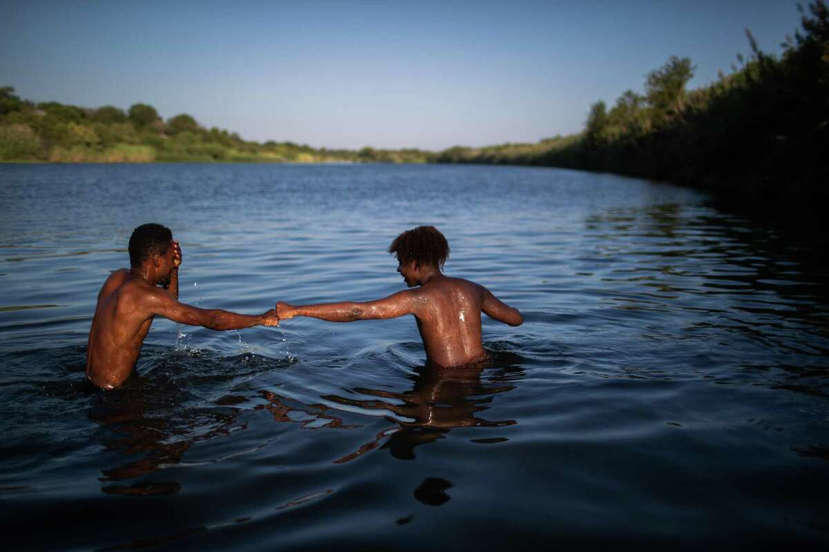 Two migrants part of the group of people from Haiti waiting in Del Rio and Ciudad Acuña to get access to the United States bump fists after finding each other in the waters of the the Rio Grande while bathing early Friday, Sept. 17, 2021, in Ciudad Acuña.