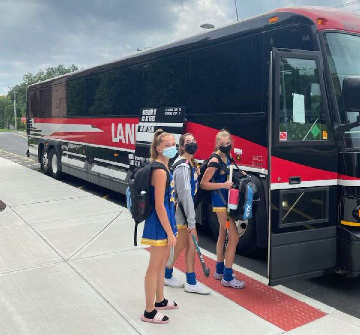 The Brookfield field hockey team boards a coach bus the Bobcats had to use to a game at Nonnewaug in Woodbury on Tuesday. Brookfield is one of many school districts that have had to find alternative modes of transportation due to a bus shortage.