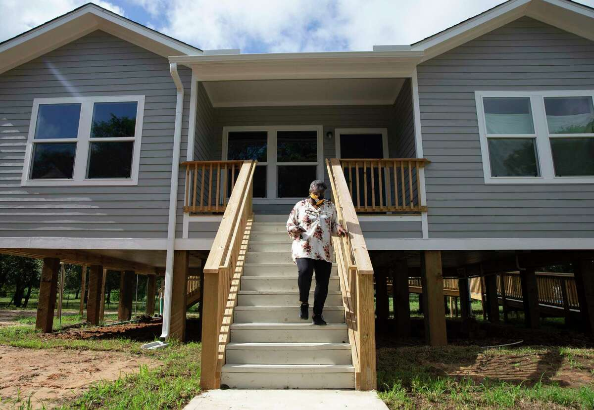 Doris Jones walks from her new home, rebuilt and raised seven feet after receiving assistance from the Texas GLO, to her sewing shop Thursday, Sept. 16, 2021, in Simonton. Her old home flooded in 2016 and again during Hurricane Harvey in 2017. It was too low to the ground and the foundation was too damaged to repair, so her home was demolished and rebuilt.