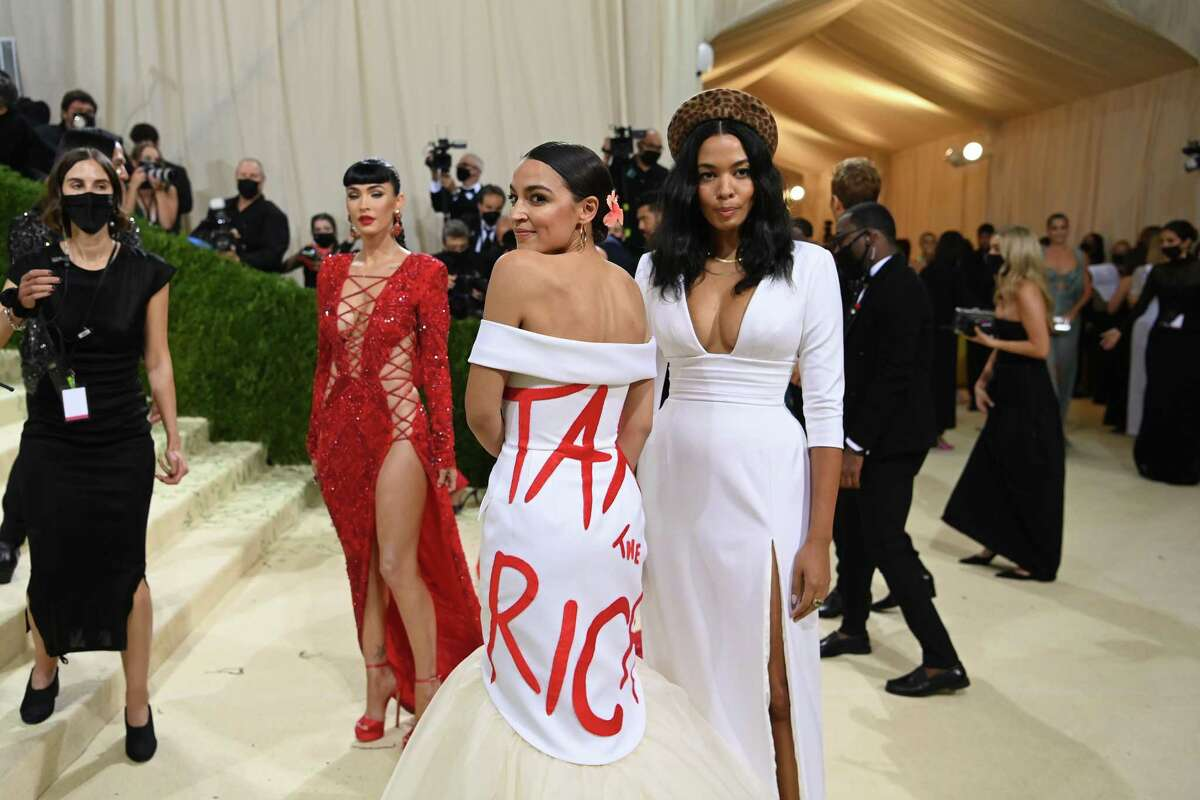 """Rep. Alexandria Ocasio-Cortez (D-N.Y.), center, at the Metropolitan Museum of Art's Costume Institute benefit gala in New York, Sept. 13, 2021. While some championed the provocation, the congresswoman's """"Tax the Rich"""" gown drew sharp statements from across the political spectrum. (Nina Westervelt/The New York Times)"""