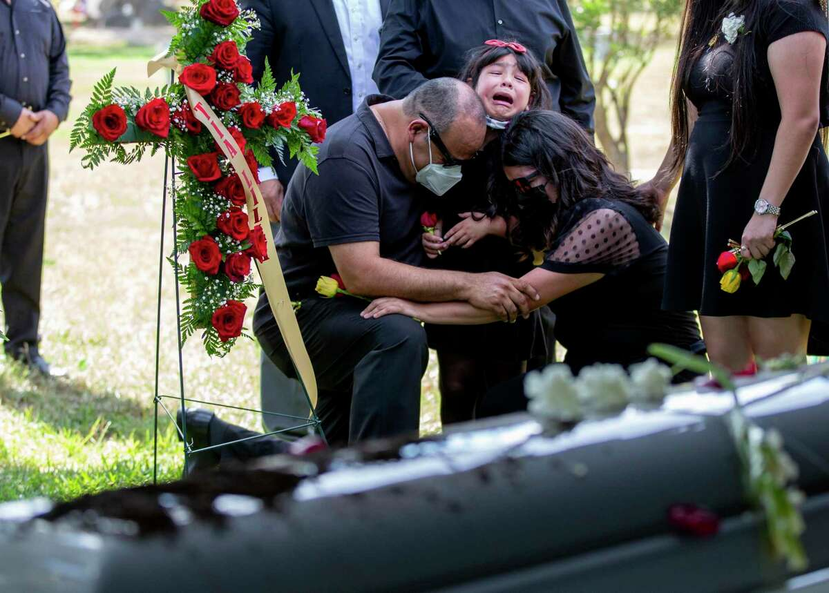 Sergio Gonzalez and daughters Sophia and Destiny embrace near the coffin of wife and mother Veronica Bustos Gonzalez. On Friday, family and friends gathered at Mission Park Funeral Chapels South to bury Veronica, her sister and her father, who died from COVID-19 within eight days of each other in August.