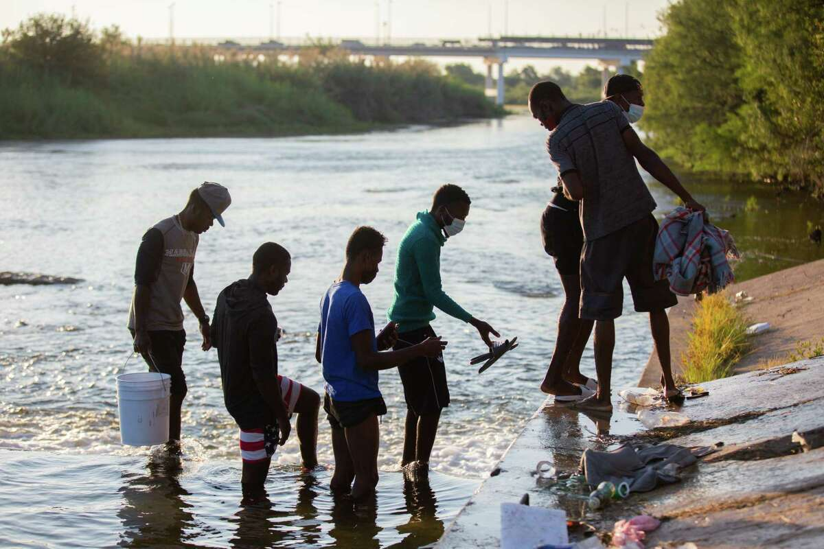 Migrants part of the group of people from Haiti waiting in Del Rio and Ciudad Acuña to get access to the United States cross the Rio Grande toward Ciudad Acuña to get supplies, Friday, Sept. 17, 2021, in Ciudad Acuña.