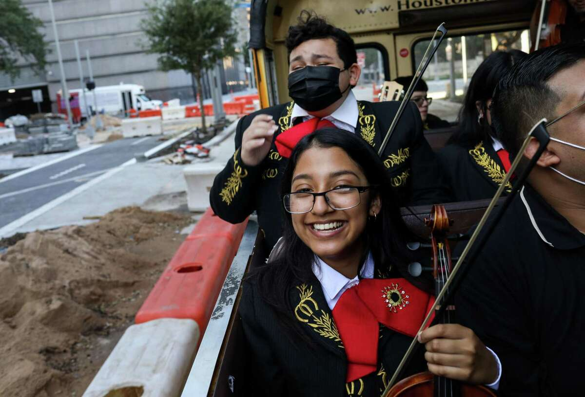 Marisa Salinas, 16, front, and Zayden Longoria, 14, laugh as they ride in an open-air school bus as part of a local news show Friday in downtown Houston.