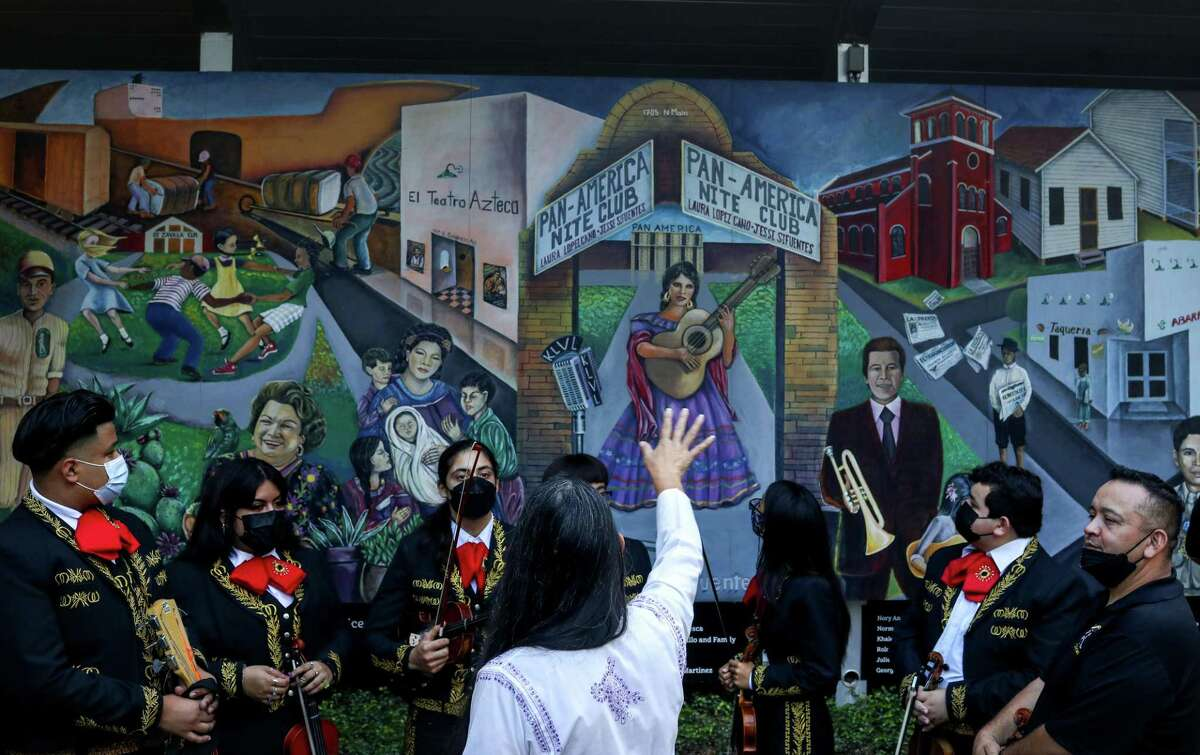 """Gracie Saenz, a former Houston City Councilmember, talks about the mural """"Mexican-American History & Culture in 20th Century Houston,"""" as she speaks to a group of students from the Sam Houston Math, Science and Technology Center High School Mariachi Band on Friday, Sept. 17, 2021, at Sam Houston Park in Houston in Houston."""