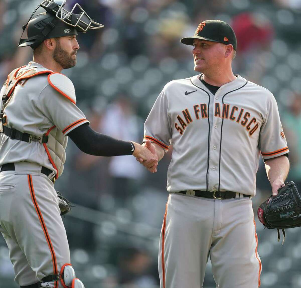 San Francisco Giants catcher Curt Casali, left, congratulates relief pitcher Jake McGee after the team's baseball game against the Colorado Rockies on Wednesday, Sept. 8, 2021, in Denver. The Giants won 7-4. (AP Photo/David Zalubowski)