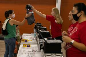Dow RunWalk participants pick up race materials inside the Curling Center of the Greater Midland Community Center the day before the race, Friday, Sept. 17, 2021. (Drew Travis/for the Daily News)