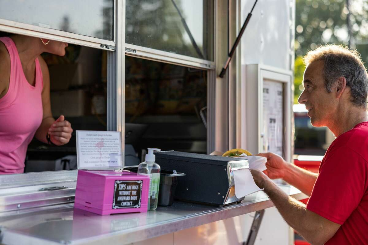Tim Fish, race volunteer, receives a taco from a vendor at the Eat Great food festival during packet pickup for the Dow RunWalk the day before the race, Friday, Sept. 17, 2021 at the Midland Community Center. (Drew Travis/for the Daily News)
