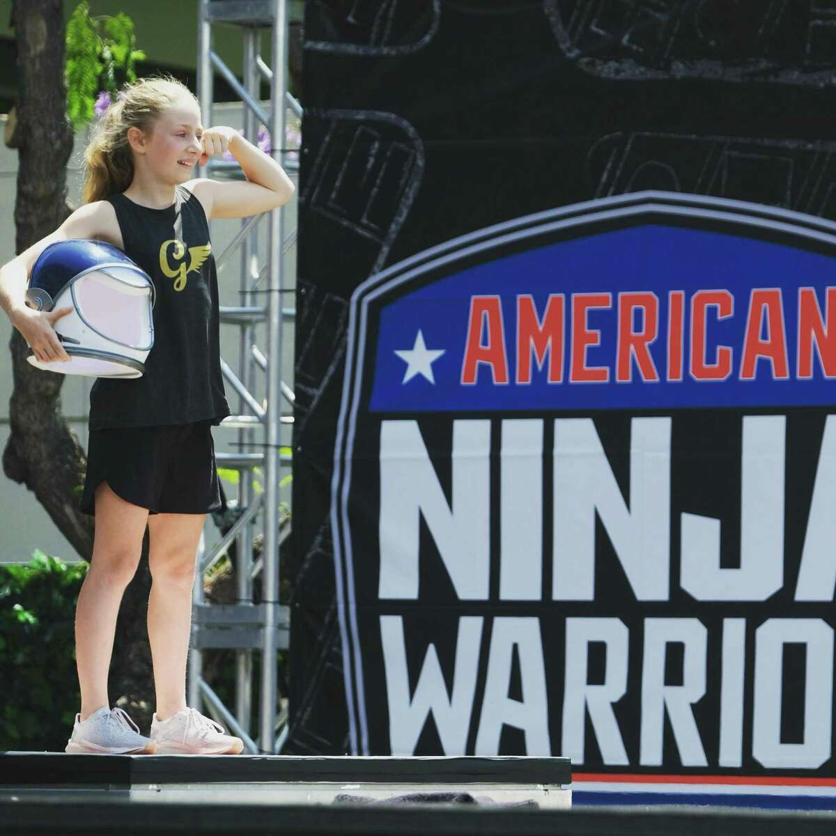 """Wilchester Elementary School fifth grader Grace Schneider brought an astronaut helmet to the starting line of her race on the Peacock show American NInja Warrior Junior. Her shirt displays her nickname, """"The Flying G."""""""