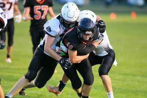 Ubly quarterback Evan Peruski (10) tries to reach toward the goal line as he's tackled by a couple of Harbor Beach defenders.