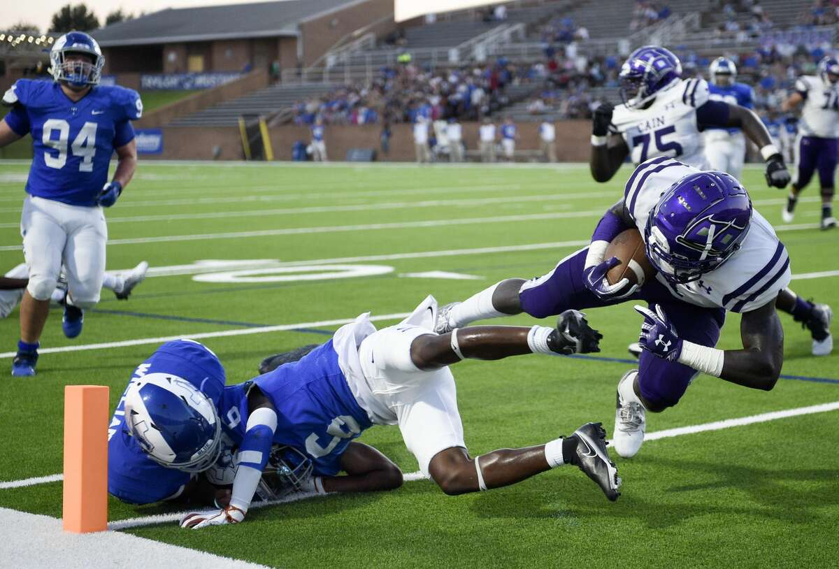Klein Cain running back Ramir McCray, right, falls into the end zone for a touchdown during the first half of a high school football game against Katy Taylor, Friday, Sept. 17, 2021, in Katy.