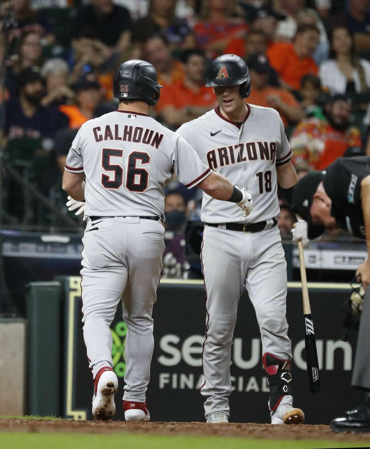 Arizona Diamondbacks designated hitter Kole Calhoun (56) celebrates his home runwith Carson Kelly (18) during the sixth inning of an MLB baseball game at Minute Maid Park, Friday, September 17, 2021, in Houston.