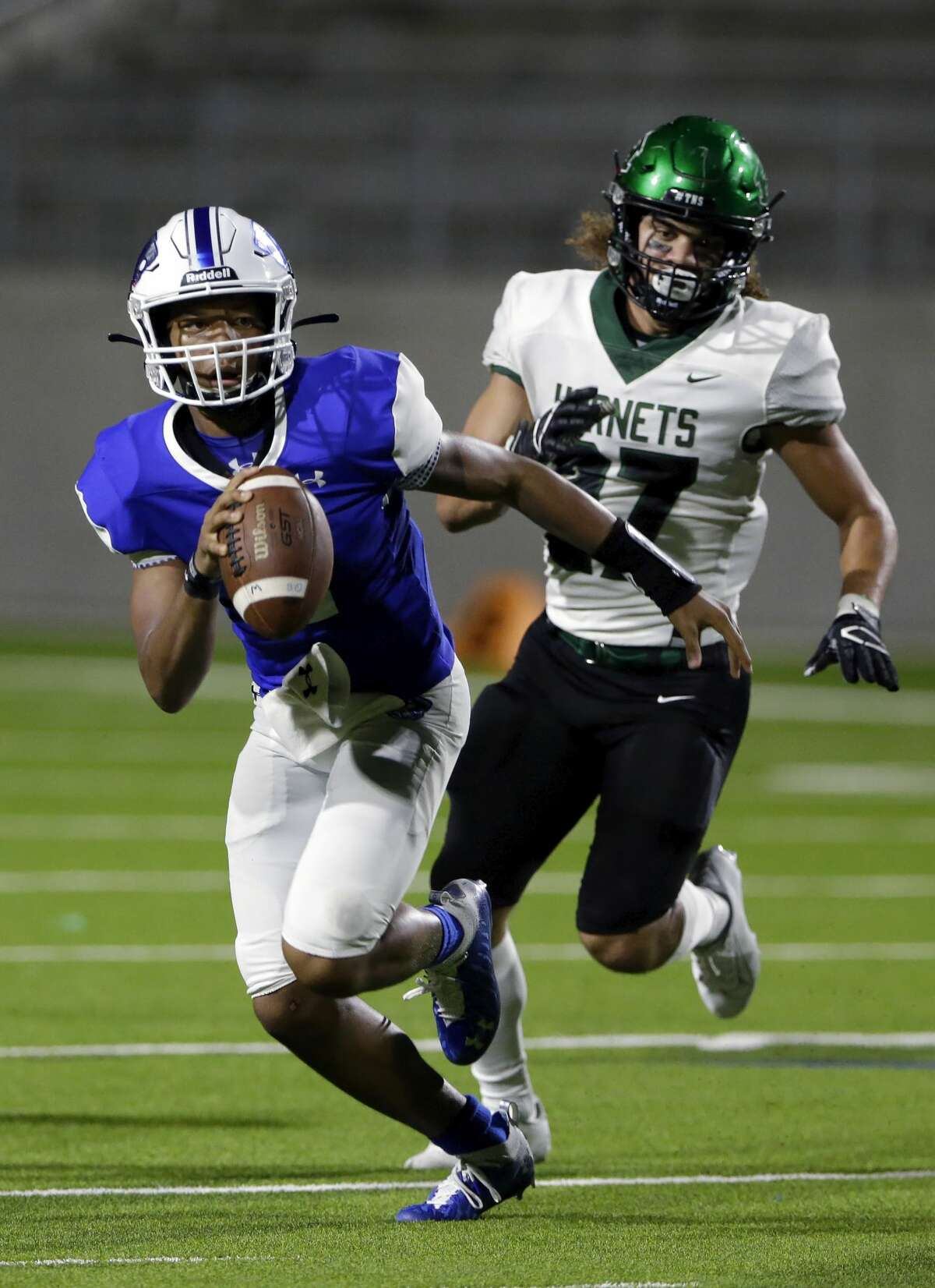 C.E. King quarterback Nehemiah Brousard, left, runs to avoid the sack by Huntsville defensive lineman Arthur Sandles (27) during the first half of a high school football game at Panther Stadium Friday, Sept. 17, 2021 in Houston, TX.