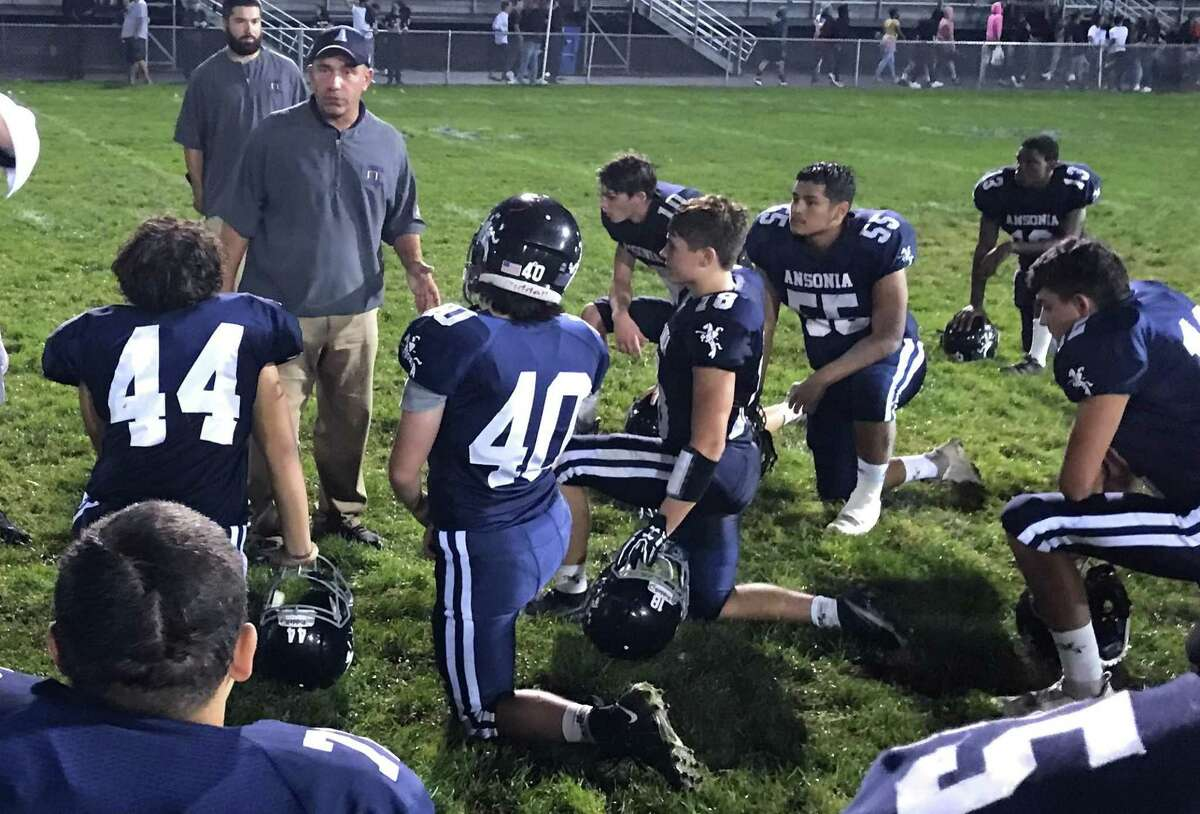 Ansonia coach Tom Brockett talks to team following its 28-13 victory over Oxford.