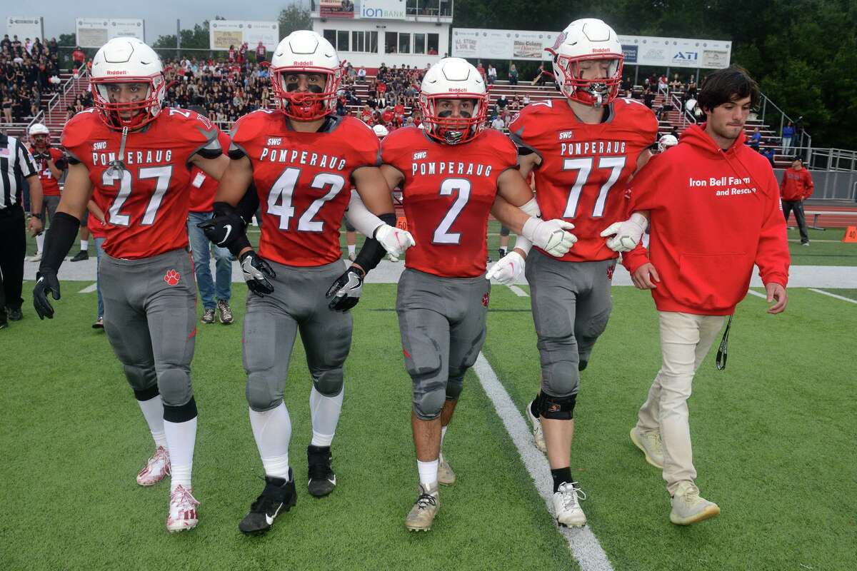 Patrick Rutledge, right, Ryan Rutledge's twin brother walks with members of the Pomperaug High School football team as they approach for the coin toss before a game against Bunnell High School, in in Southbury, Conn. Sept. 17, 2021. Ryan Rutledge, who was a member of the Pomperaug football team, was killed in an automobile accident in April.