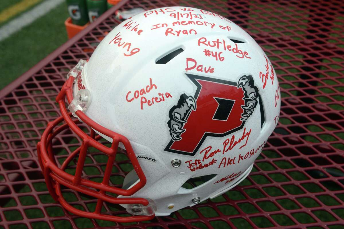 A signed Pomperaug High School football helmet was presented to Ryan Rutledge's parents prior to a game in Southbury, Conn. Sept. 17, 2021.