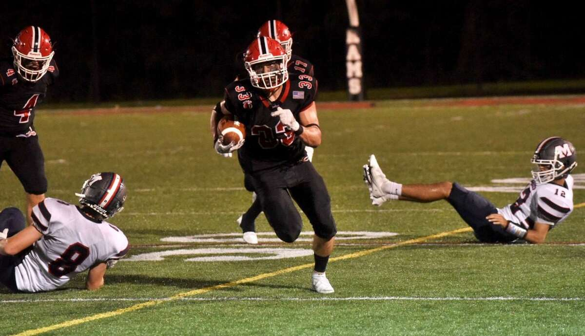 New Canaan's Hunter Telesco (33) carries the ball during a football game against Brien McMahon on Friday, Sept. 17, 2021 at Dunning Stadium in New Canaan.